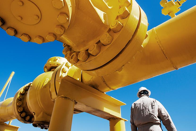 oil refinery worker standing next to yellow pipeline